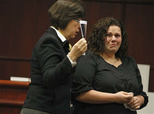 Meredith Fisher, sister of Michelle Young, right, tears up as she looks at evidence photos held by Assistant District Attorney Becky Holt during Jason Young&#39;s retrial on Tuesday, Feb. 7, 2012 in Raleigh, N.C.  <span class=meta>(AP Photo&#47; Shawn Rocco)</span>