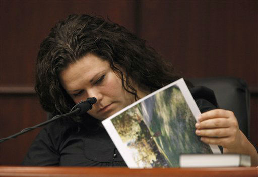 Meredith Fisher, sister of Michelle Young, looks at evidence photos during Jason Young&#39;s retrial on Tuesday, Feb. 7, 2012 in Raleigh, N.C.  <span class=meta>(AP Photo&#47; Shawn Rocco)</span>