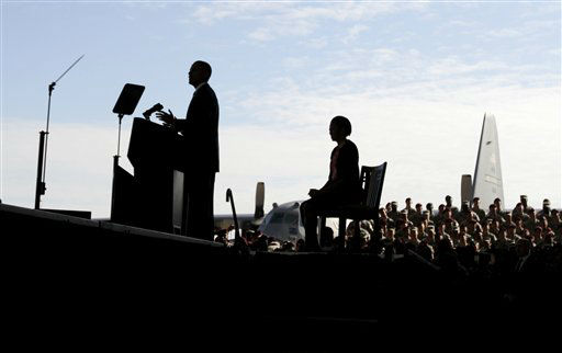 A silhouetted President Barack Obama, accompanied by first lady Michelle Obama, speaks at Fort Bragg, N.C., Wednesday, Dec. 14, 2011.  <span class=meta>(AP Photo&#47; Carolyn Kaster)</span>