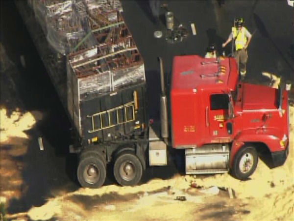 Firefighters clean up spilled fuel Friday after a tractor-trailer and a BMW collided at the top of the on-ramp at U.S. 1 and New Hill Holleman Rd. in Southwest Wake County. <span class=meta>(WTVD Photo&#47; Chopper 11 HD)</span>
