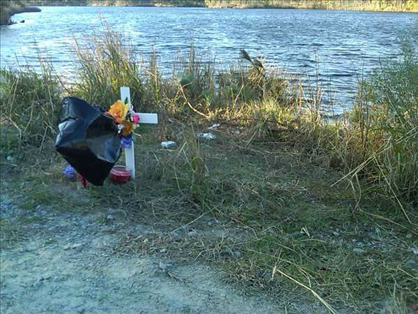 "<div class=""meta ""><span class=""caption-text "">An impromptu memorial is set up for Brenton Briggs on the shore at Boundary Line Lake off McArthur Road at Fort Bragg. (WTVD Photo/ Gilbert Baez)</span></div>"