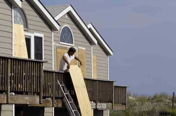 Justin Curcio, a carpenter from Buxton, boards up windows and doors at Hatteras Cabanas in Hatteras, N.C., Wednesday, Sept. 1, 2010 as Hurricane Earl approaches North Carolina&#39;s Outer Banks.  <span class=meta>(AP Photo&#47; Gerry Broome)</span>
