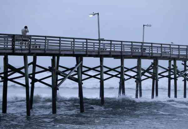 A man walks down a pier as the surf crashes around him as Hurricane Earl heads toward the eastern coast in Atlantic Beach, N.C., Thursday, Sept. 2, 2010.  <span class=meta>(AP Photo&#47; Chuck Burton)</span>