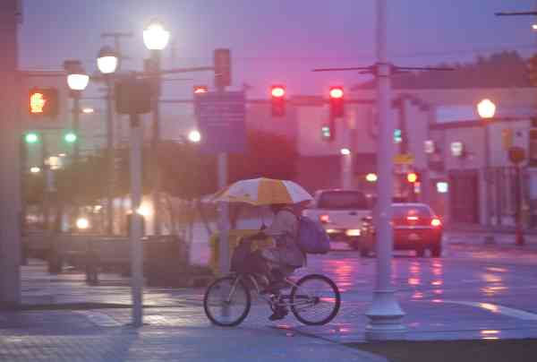 A man uses an umbrella while riding his bike as Hurricane Earl churns up the eastern coast on Friday, Sept.  3, 2010 in Virginia Beach, Va.  <span class=meta>(AP Photo&#47; Evan Vucci)</span>