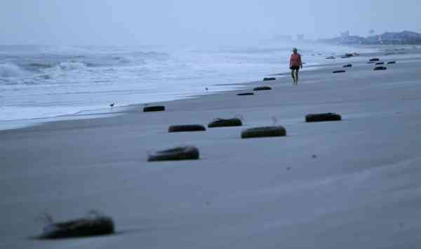 A woman walks on the beach past tires washed up after Hurricane Earl brushed the North Carolina coast in Atlantic Beach, N.C., Friday, Sept. 3, 2010.  <span class=meta>(AP Photo&#47; Chuck Burton)</span>