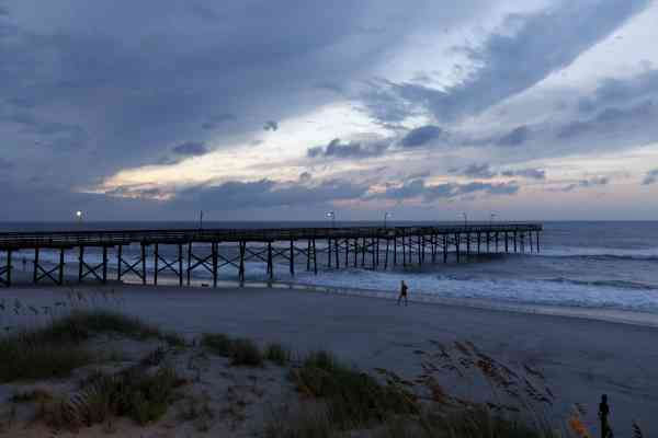 A woman walks on the beach near a pier slightly damaged after Hurricane Earl brushed the North Carolina coast in Atlantic Beach, N.C., Friday, Sept. 3, 2010. <span class=meta>(AP Photo&#47; Chuck Burton)</span>