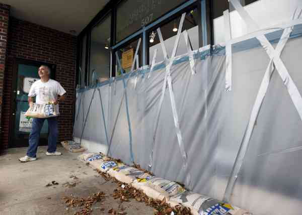 R.V. Hodge removes sandbags from a storefront  in Beaufort, N.C., as residents return to business as usual after Hurricane Earl brushed past the North Carolina coast Friday, Sept. 3, 2010.  <span class=meta>(AP Photo&#47; Chuck Burton)</span>