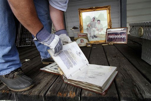 "<div class=""meta ""><span class=""caption-text "">Bill Davis looks through a binder with family letters and photos as he cleans out his storage unit after floodwaters receded in Windsor, N.C., Monday, Oct. 4, 2010.  (AP Photo/ Jim R. Bounds)</span></div>"