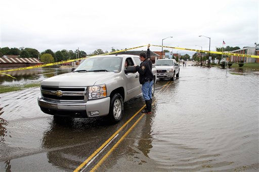 "<div class=""meta ""><span class=""caption-text "">Windsor Police Officer Sgt. R.L. Morris speaks with business owners as they leave the floodwaters in Windsor, N.C., Monday, Oct. 4, 2010.  (AP Photo/ Jim R. Bounds)</span></div>"
