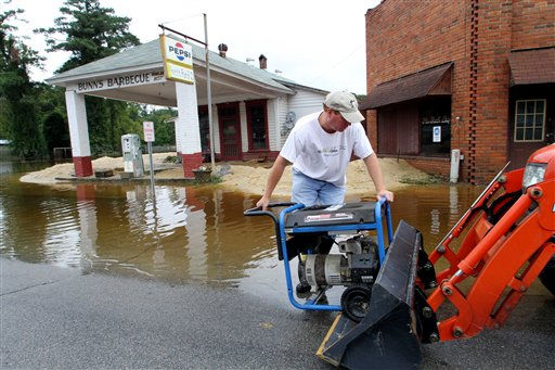 "<div class=""meta ""><span class=""caption-text "">Randy Russell loads a generator into a front loader to carry it over to this restaurant, Bunn's Barbecue, as floodwaters recede in Windsor, N.C., Monday, Oct. 4, 2010.  (AP Photo/ Jim R. Bounds)</span></div>"