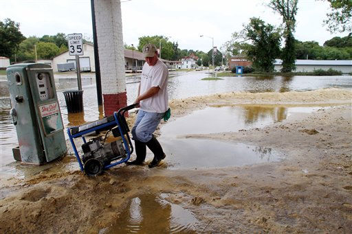 "<div class=""meta ""><span class=""caption-text "">Randy Russell pulls a generator up to his restaurant, Bunn's Barbecue, as receding floodwaters leak over makeshift sand barriers in Windsor, N.C., Monday, Oct. 4, 2010.  (AP Photo/ Jim R. Bounds)</span></div>"