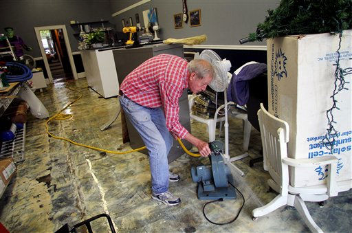 "<div class=""meta ""><span class=""caption-text "">Ted Shaw cleans up The Pool & Spa Shop after floodwaters receded in Windsor, N.C., Sunday, Oct. 3, 2010.  (AP Photo/ Jim R. Bounds)</span></div>"