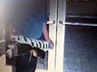 Police say this image shows the thief leaving the building with the art work. <span class=meta>(UNC Department of Public Safety Photo)</span>