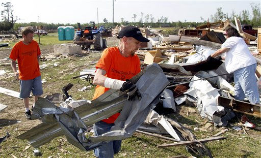 Arthur Tronnes, center, removes debris from a destroyed home in Askewville, N.C., Tuesday, April 19, 2011 after tornados devastated the area Saturday.  <span class=meta>(AP Photo&#47; Jim R. Bounds)</span>