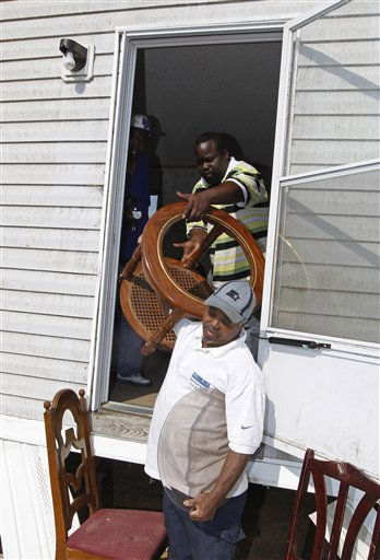 Phillip Sellers Jr, top, hands furniture to his father, Phillip Sellers Sr., bottom, as they remove belongings from their damaged home at a mobile home community in Dunn, N.C., Tuesday, April 19, 2011, after a tornado ripped through the area Saturday.  <span class=meta>(AP Photo&#47; Chuck Burton)</span>