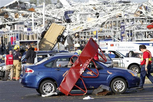 "<div class=""meta ""><span class=""caption-text "">FILE - Emergency personnel work around a Lowes Home Improvement store after it was hit by a tornado in Sanford, N.C., Saturday, April 16, 2011.  (AP Photo/ Jim R. Bounds)</span></div>"