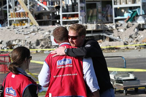 Lowe&#39;s store manager Mike Hollowell, center, who directed dozens of customers to safety when a tornado struck the Sanford, NC, hardware store the previous day, gets a hug on Sunday, April 17, 2011, from co-worker Don Wear, who was also in the store when the storm hit.  <span class=meta>(AP Photo&#47; Ted Richardson)</span>
