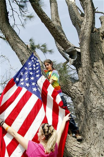 Morgan Barfield right, and Madson Barfield hang their grandfather&#39;s  WWll American flag from a tree at her grandmother&#39;s home in Colerain, N.C., Monday, April 18, 2011 after a tornado ripped through the area Saturday.  <span class=meta>(AP Photo&#47; Jim R. Bounds)</span>