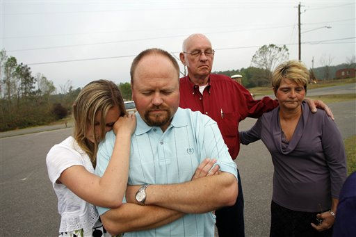 Randall Godfrey, second from left, and daughter Brooke pray during Easter sunrise service at Kendale Acres Free Will Baptist Church in Sanford, N.C., Sunday, April 24, 2011. The church is just about the only structure still standing in the neighborhood after tornados ripped through the area last week.   <span class=meta>(AP Photo&#47; Jim R. Bounds)</span>