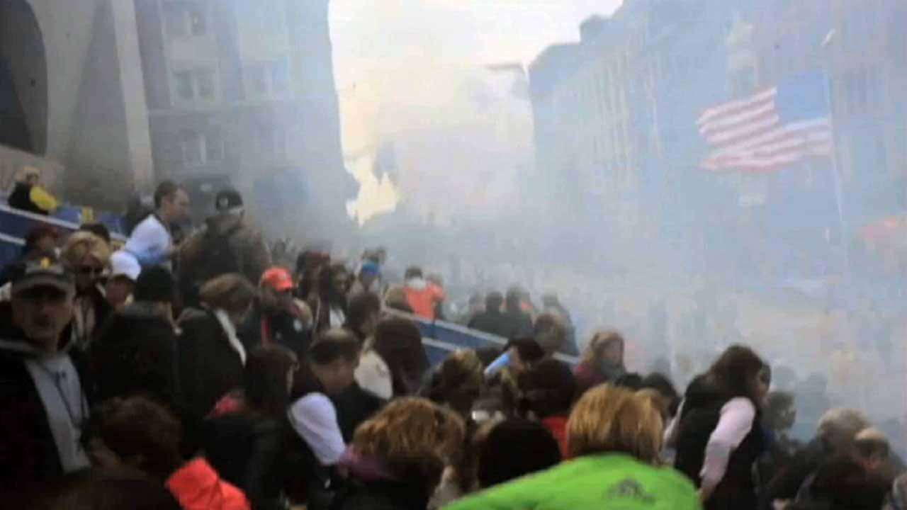 In this image from video provided by Ryan Hoyme, the second explosion can be seen in the distance as smoke from the first explosion surrounds spectators exiting the stands during the Boston Marathon in Boston, Monday, April 15, 2013.AP Photo/Ryan Hoyme
