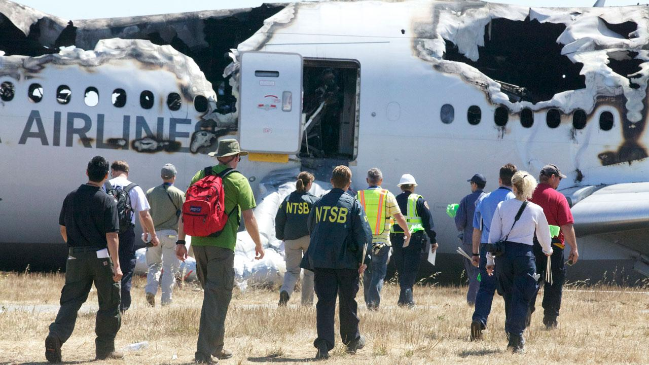 In this image provided by the NTSB, investigators examine the wreckage at the scene of the Asiana Airline crash Sunday July 7, 2013.AP Photo/NTSB
