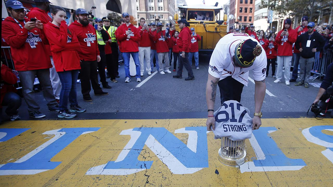 Boston Red Soxs Jonny Gomes places the championship trophy and a Red Sox baseball jersey at the Boston Marathon Finish Line during a pause in their World Series victory rolling rally in Boston <span class=meta>(Elise Amendola)</span>