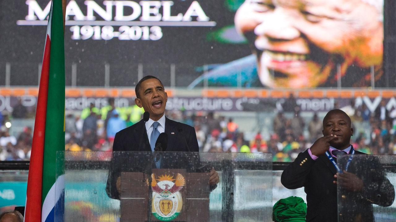 President Barack Obama delivers his speech next to a sign language interpreter during a memorial service at FNB Stadium in honor of Nelson Mandela on Tuesday, Dec. 10, 2013 in Soweto, near Johannesburg.AP Photo/ Evan Vucci