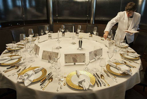 "<div class=""meta ""><span class=""caption-text "">Evan Boyle sets menu cards during a re-creation of the final first class dinner served on the RMS Titanic, Saturday, April 14, 2012, in Houston. The Titanic sank in the North Atlantic Ocean April 15, 1912 after colliding with an iceberg during her maiden voyage from Southampton, England to New York. (AP Photo/Dave Einsel)</span></div>"