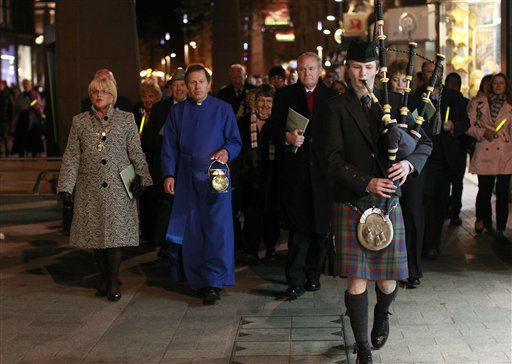 "<div class=""meta image-caption""><div class=""origin-logo origin-image ""><span></span></div><span class=""caption-text"">Dean John Mann, second from left, and Northern Ireland Deputy First Minister Martin McGuinness, center, walk behind a lone bagpiper to Belfast City Hall following a Titanic Commemoration service at St. Ann's Cathedral Belfast, Northern Ireland, Saturday, April 14, 2012.  A century after the great ship went down with the loss of 1,500 lives, events around the globe are marking a tragedy that retains a titanic grip on the world's imagination _ an icon of Edwardian luxury that became, in a few dark hours 100 years ago, an enduring emblem of tragedy. (AP Photo/Peter Morrison)</span></div>"