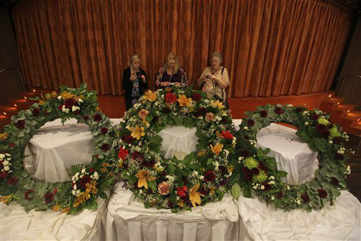 "<div class=""meta ""><span class=""caption-text "">People stand behind wreaths prepared for a ceremony in the memory of the Titanic victims as the MS Balmoral Titanic memorial cruise ship approaches the wreck site of the Titanic in the Atlantic Ocean, Saturday, April 14, 2012. A century after the great ship went down with the loss of 1,500 lives, events around the globe are marking a tragedy that retains a titanic grip on the world's imagination _ an icon of Edwardian luxury that became, in a few dark hours 100 years ago, an enduring emblem of tragedy. (AP Photo/Lefteris Pitarakis)</span></div>"