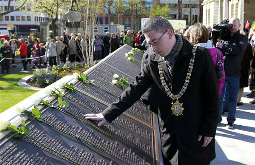 Belfast Lord Mayor Niall Ó Donnghaile looks at the names of the victims who died in the Titanic disaster on the Titanic Memorial Plaque during a service at Belfast City Hall, Northern Ireland, Sunday, April 15, 2012.    The Titanic passenger liner was built in Belfast, and sank in the North Atlantic Ocean on its maiden voyage from England to New York, USA, in the early hours of April 15, 1912, after colliding with an iceberg and over 1,500 people perished in the sinking. (AP Photo/Peter Morrison)