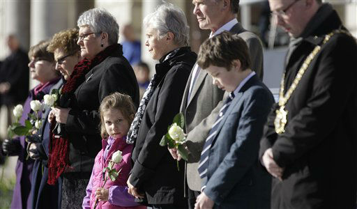 Six-year old Alex Warouaon from Chicago, USA,  who's great-great-great-grandfather died in the Titanic disaster, holds a rose during a minute silence at the Titanic Memorial Plaque during the service at Belfast City Hall, Northern Ireland, Sunday, April 15, 2012 one-hundred years after the Titanic sank.  The Titanic passenger liner was built in Belfast, and sank in the North Atlantic Ocean on its maiden voyage from England to New York, USA, in the early hours of April 15, 1912, after colliding with an iceberg and over 1,500 people perished in the sinking. (AP Photo/Peter Morrison)