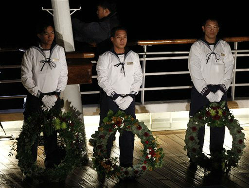 "<div class=""meta ""><span class=""caption-text "">Crew members stand with wreaths during a memorial service, marking the 100th year anniversary of the Titanic disaster, aboard the MS Balmoral Titanic memorial cruise ship, at the wreck site in the North Atlantic Ocean, early Sunday, April 15, 2012.   Cruise ship passengers and crew said prayers Sunday at the spot in the North Atlantic where the Titanic sank 100 years ago with the loss of more than 1,500 lives. (AP Photo/Lefteris Pitarakis)</span></div>"
