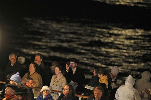 Passengers participate in a memorial service, marking the 100th year anniversary of the Titanic disaster, aboard the MS Balmoral Titanic memorial cruise ship, at the wreck site in the North Atlantic Ocean, early Sunday, April 15, 2012.   Cruise ship passengers and crew said prayers Sunday at the spot in the North Atlantic where the Titanic sank 100 years ago with the loss of more than 1,500 lives. (AP Photo/Lefteris Pitarakis)