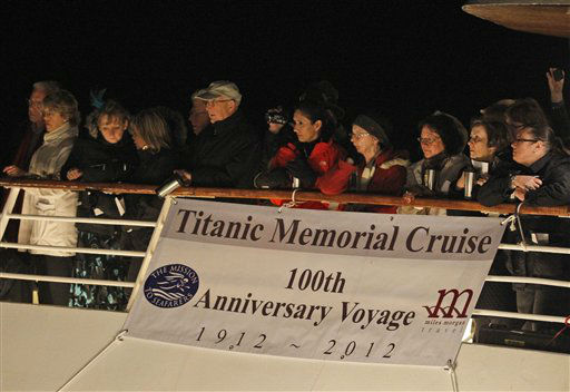 Passengers participate in a memorial service, marking the 100th year anniversary of the Titanic disaster, aboard the MS Balmoral Titanic memorial cruise ship, at the wreck site in the North Atlantic Ocean, early Sunday, April 15, 2012. Aboard the Balmoral, a cruise ship taking history buffs and descendants of Titanic victims on the route of the doomed voyage, passengers and crew hold two ceremonies at the site of the disaster, 640 kilometers (400 miles) off the coast of Newfoundland - one marking the time when the ship hit the iceberg, the other the moment it sank below the waves. (AP Photo/Lefteris Pitarakis)