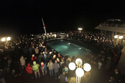 "<div class=""meta image-caption""><div class=""origin-logo origin-image ""><span></span></div><span class=""caption-text"">Passengers participate in a memorial service, marking the 100th year anniversary of the Titanic disaster, aboard the MS Balmoral Titanic memorial cruise ship, at the wreck site in the North Atlantic Ocean, early Sunday, April 15, 2012. Aboard the Balmoral, a cruise ship taking history buffs and descendants of Titanic victims on the route of the doomed voyage, passengers and crew hold two ceremonies at the site of the disaster, 640 kilometers (400 miles) off the coast of Newfoundland - one marking the time when the ship hit the iceberg, the other the moment it sank below the waves. (AP Photo/Lefteris Pitarakis)</span></div>"