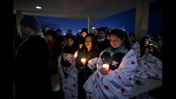 Residents hold a candlelight vigil outside Newtown High School after President Barack Obama delivered remarks at an int