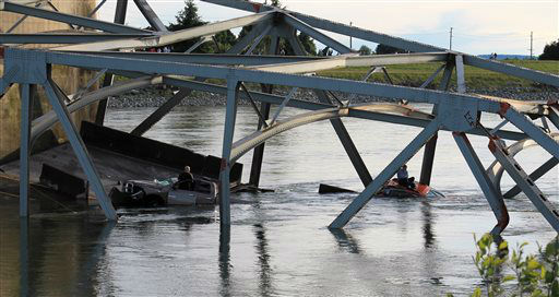 In this photo provided by Francisco Rodriguez, one man is seen sitting atop a car that fell into the Skagit River another stands in the door of his partially submerged pickup truck after the collapse of the Interstate 5 bridge there minutes earlier Thursday, May 23, 2013, in Mount Vernon, Wash. &#40;AP Photo&#47;Francisco Rodriguez&#41; <span class=meta>(AP Photo&#47; Francisco Rodriguez)</span>