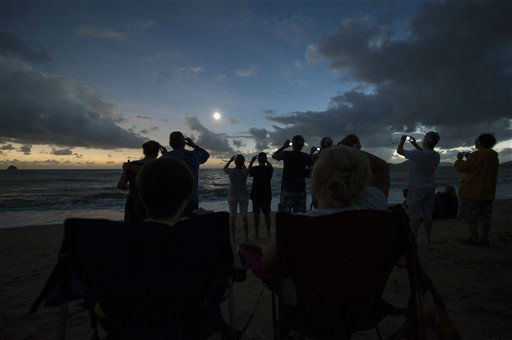 In this photo released by Tourism Queensland, people gather on Palm Cove beach in Queensland state, Australia, to watch a total solar eclipse Wednesday, Nov. 14,