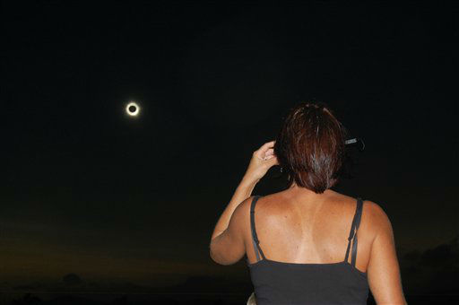 In this photo provided by Tourism Queensland, a woman watches a total solar eclipse at Lakeland in Queensland state, Australia, Wednesday, Nov. 14, 2012. Starting just after dawn, the eclipse cast its 150-kilometer &#40;95-mile&#41; shadow in Australia&#39;s Northern Territory, crossed the northeast tip of the country and was swooping east across the South Pacific, where no islands are in its direct path. <span class=meta>(AP Photo&#47; David Barker)</span>