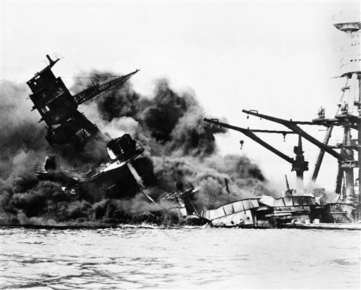 The battleship USS Arizona belches smoke as it topples over into the sea during Japanese surprise attack on Pearl Harbor, Hawaii, December 7, 1941. The ship sank with more than 80 percent of its 1,500-man crew, including Rear Admiral Issac C. Kidd. The attack, which left 2,343 Americans dead and 916 missing, broke the backbone of the U.S. Pacific Fleet and forced America out of a policy of isolationism. President Franklin D. Roosvelt announced that it was &#34;a date which will live in infamy&#34; and Congress declared war on Japan the morning after. This was the first attack on American territory since 1812.  <span class=meta>(AP Photo&#47; XJFM)</span>