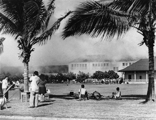 **FILE PHOTO** In this Dec. 7, 1941, file photo, students of the Lunalilo High School in the Waikiki district of Honolulu watch their school burn after the roof of the main building, at center, was hit by a bomb during the Japanese attack on Pearl Harbor, Hawaii.   <span class=meta>(AP Photo)</span>