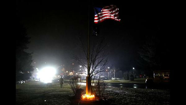 A young boy places a candle with others at the base of a flagpole outside Newtown High School before an interfaith vigil with President Barack Obama, Sunday, Dec. 16, 2012, in Newtown, Conn.  <span class=meta>(AP Photo&#47;Jason DeCrow)</span>