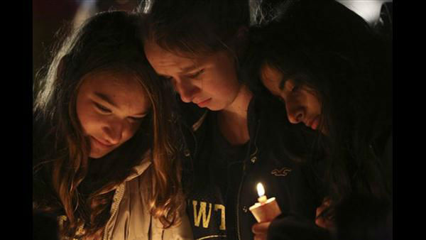 Kate Suba, left, Jaden Albrecht, center, and Simran Chand pay their respects at one of the makeshift memorials in honor of the victims of the Sandy Hook Elementary School shooting, Sunday, Dec. 16, 2012, in Newtown, Conn. <span class=meta>(AP Photo&#47;Mary Altaffer)</span>