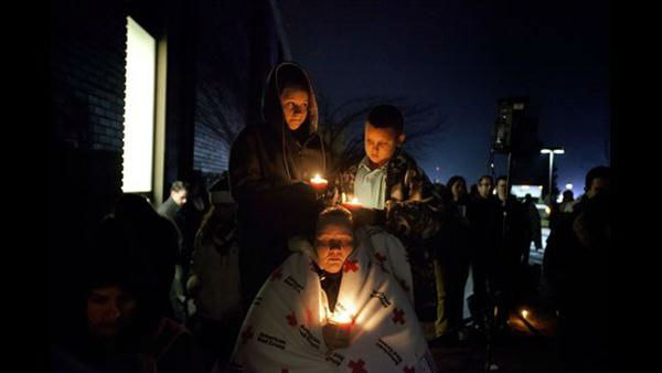Sharon Bertrand, center, listens with her daughter Daysha, 13, left, and son Juan, all of Waterbury, Conn., to a memorial service over a loudspeaker outside Newtown High School for the victims of the Sandy Hook Elementary School shooting, Sunday, Dec. 16, 2012, in Newtown, Conn.  <span class=meta>(AP Photo&#47;David Goldman)</span>