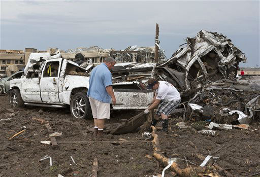 Two men go through the damage surrounding the Moore Medical Center and damaged vehicles after a tornado moves through Moore, Okla. on Monday, May 20, 2013. &#40;AP Photo&#47;Alonzo Adams&#41; <span class=meta>(AP Photo&#47; Alonzo Adams)</span>