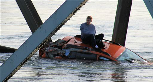 In this photo provided by Francisco Rodriguez, a man is seen sitting atop a car that fell into the Skagit River after the collapse of the Interstate 5 bridge there minutes earlier Thursday, May 23, 2013, in Mount Vernon, Wash. &#40;AP Photo&#47;Francisco Rodriguez&#41; <span class=meta>(AP Photo&#47; Francisco Rodriguez)</span>