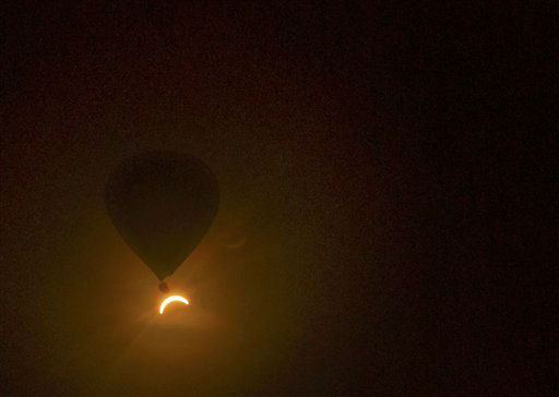 In this photo provided by Tourism Queensland, a hot air balloon floats in the air as a solar eclipse is observed near Cairns, in Queensland state, Australia, Wednesday, Nov. 14, 2012. Starting just after dawn, the eclipse cast its 150-kilometer &#40;95-mile&#41; shadow in Australia&#39;s Northern Territory, crossed the northeast tip of the country and was swooping east across the South Pacific, where no islands are in its direct path. <span class=meta>(AP Photo&#47; David Barker)</span>