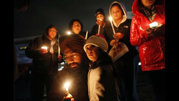 Eknoor Kaur, 3, stands with her father Guramril Singh during a candlelight vigil outside Newtown High School before an interfaith vigil with President Barack Obama, Sunday, Dec. 16, 2012, in Newtown, Conn. <span class=meta>(AP Photo&#47;Jason DeCrow)</span>