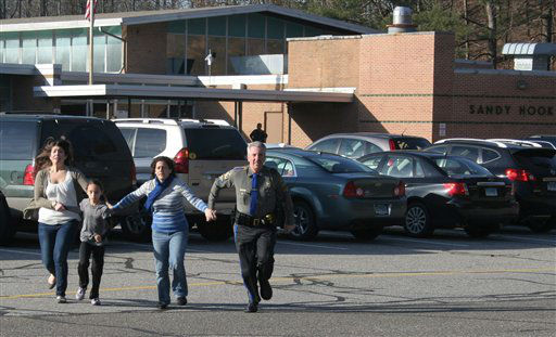 "<div class=""meta image-caption""><div class=""origin-logo origin-image ""><span></span></div><span class=""caption-text"">In this photo provided by the Newtown Bee, a police officer leads two women and a child from Sandy Hook Elementary School in Newtown, Conn., where a gunman opened fire, killing 26 people, including 20 children, Friday, Dec. 14, 2012.  (AP Photo/ Newtown Bee, Shannon Hicks)</span></div>"